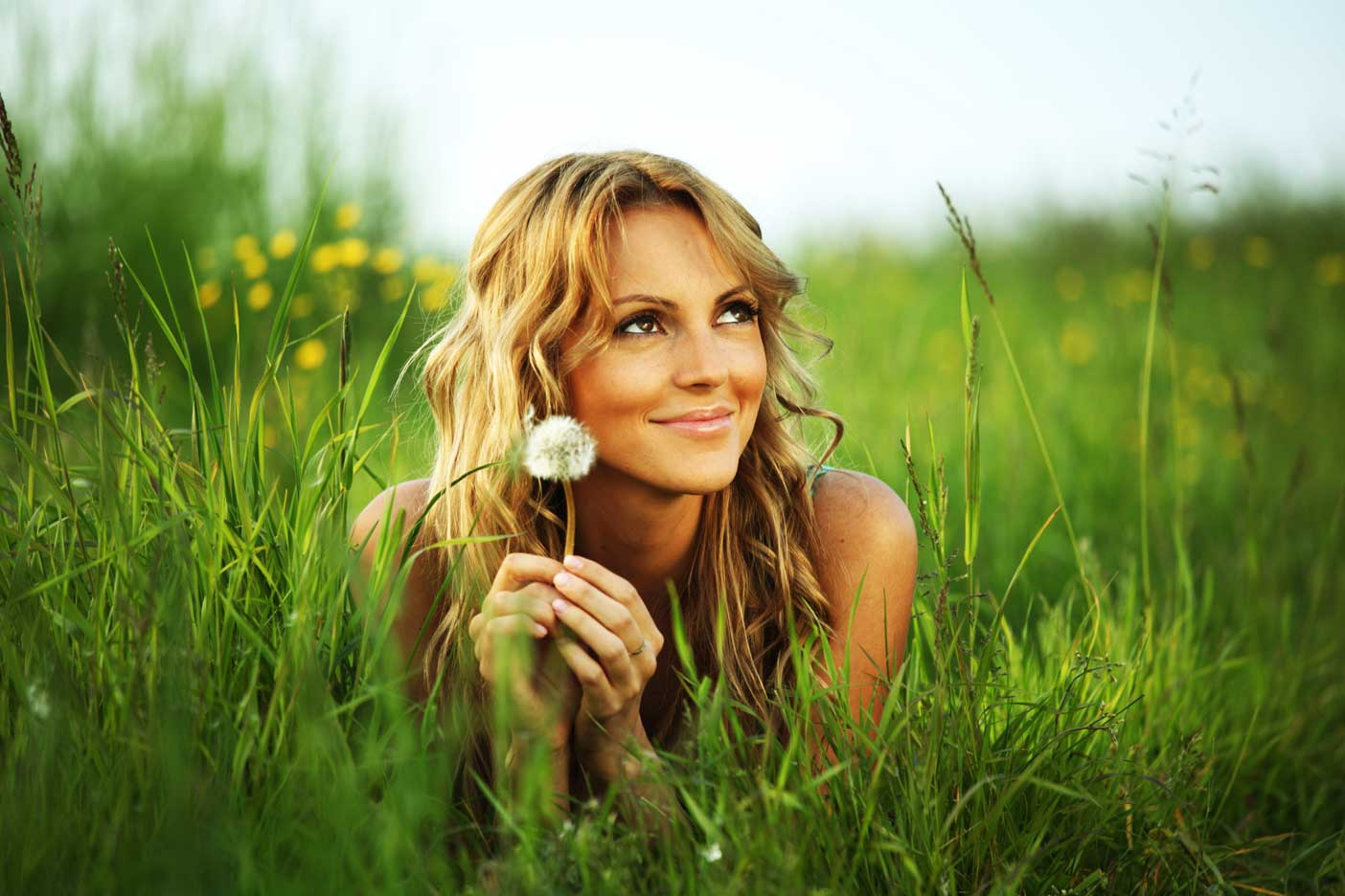 Smiling Women Laying in Grass Holding Dandelion Seed